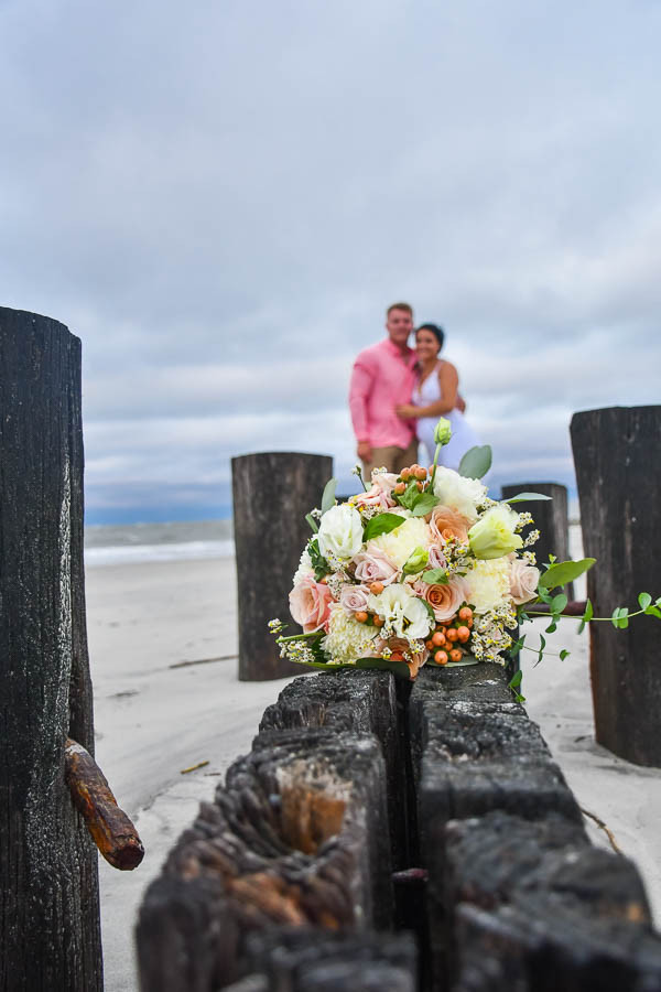 folly beach seawall elopement photo with bridal bouquet