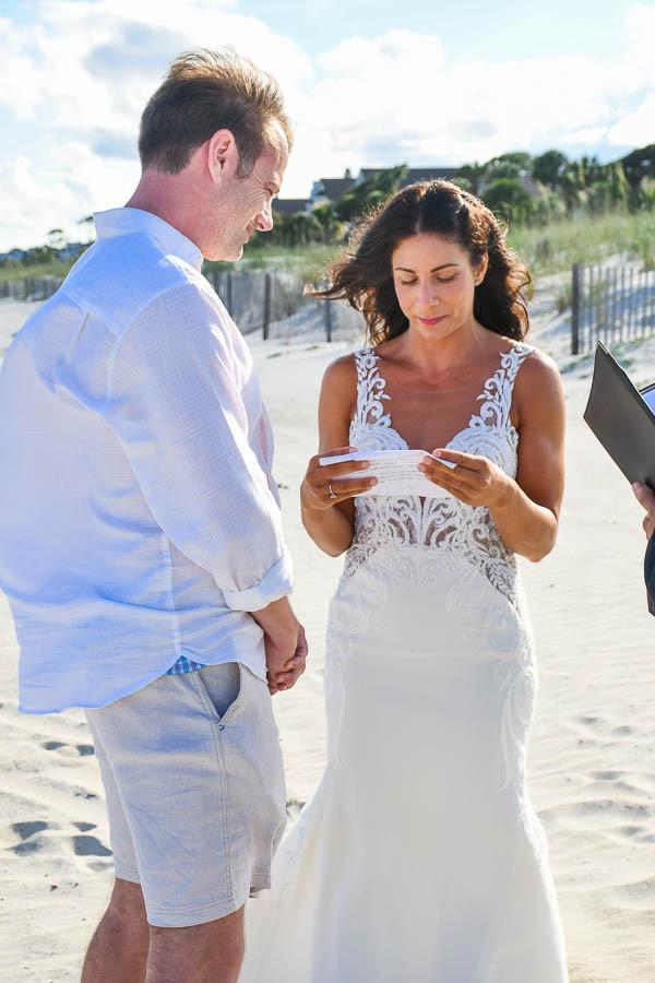 bride reading wedding vows to groom at beach wedding