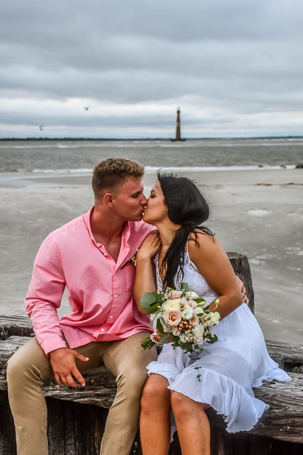 elopement kiss on the seawall at folly beach with lighthouse