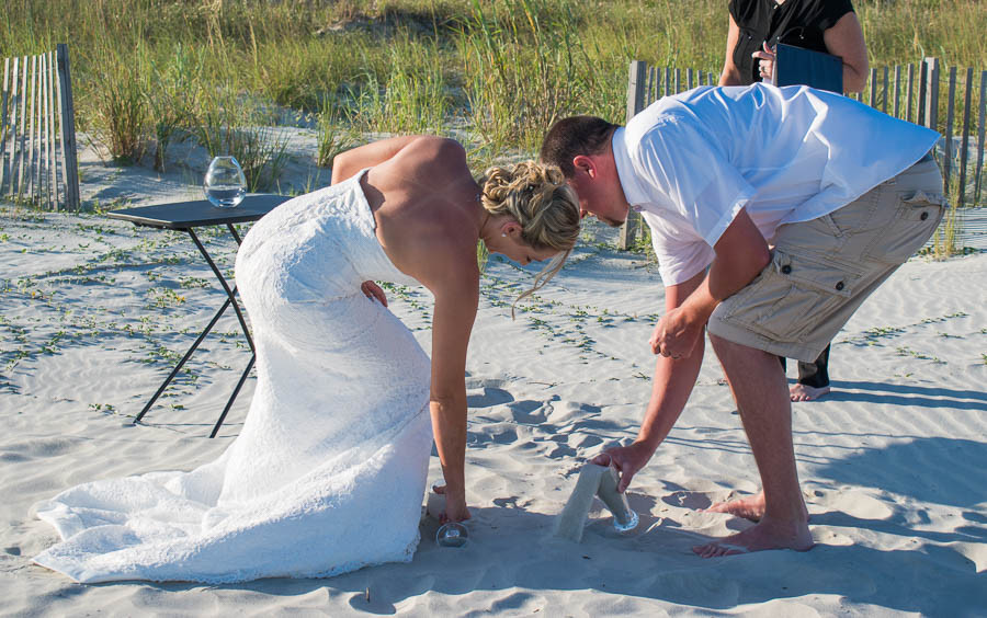 Bride and groom scoop sand from where they said their vows at a beach wedding in Charleston SC
