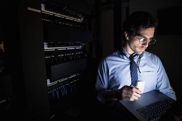 ey-man-checking-tablet-dark-server-room.jpg