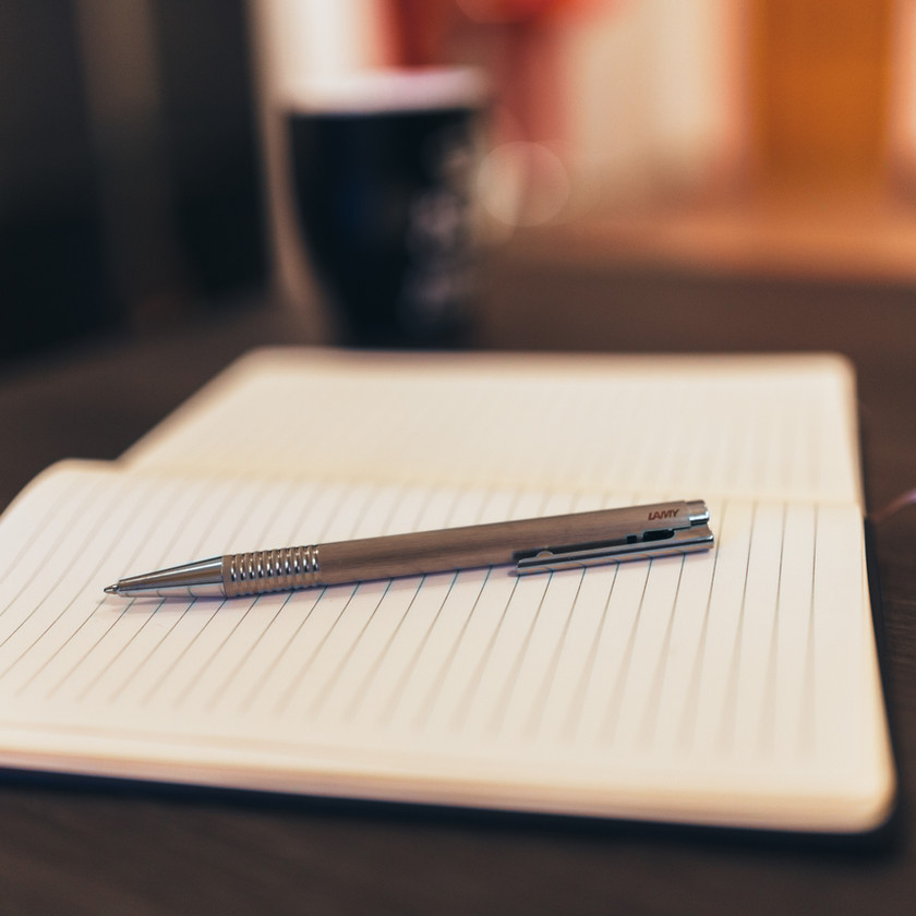 Lined notebook open with pen placed on top.