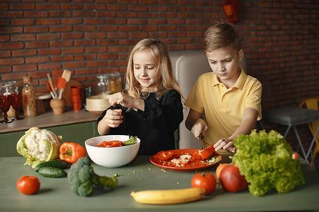 children-preparing-vegetable-salad-in-ki