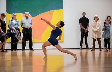 A woman in a dark blue leotard dances in