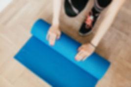 crop-young-sportswoman-unfolding-blue-yo