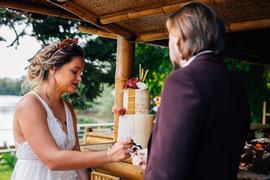 Les mariés dégustent le wedding cake, la mariée porte une robe de mariée rose sur mesure