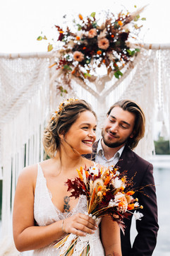 Jeune mariés lors de la cérémonie laïque, arche décoré et mariée qui porte une robe sur mesure