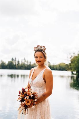 Une mariée en robe sur mesure, porte un beau bouquet de fleurs d'automne et une couronne dans les cheveux