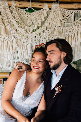Le couple devant le décor en macramé, la mariée porte une robe décolleté V