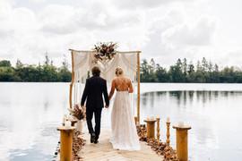 Le couple arrive devant l'arche de la cérémonie laïque, arche décoré de fleurs séchées et macramé