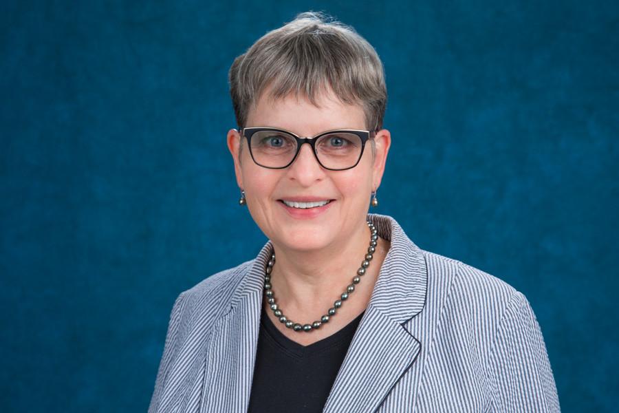 Dr. Jeanne Glidden Prickett in front of blue background.