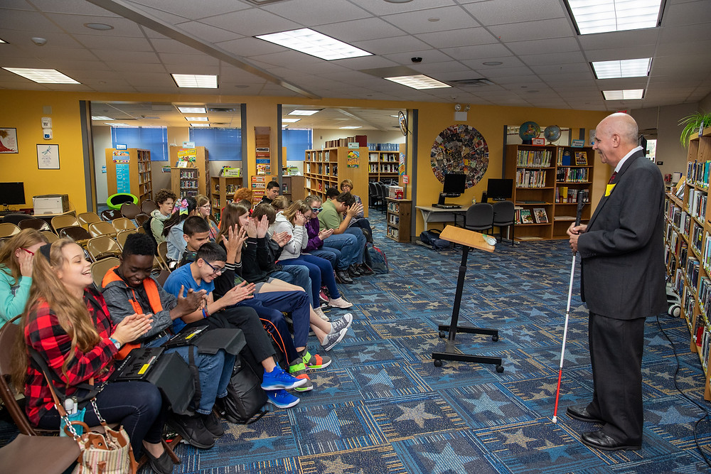 Students clapping during Mr. Crosby's presentation in the blind library.