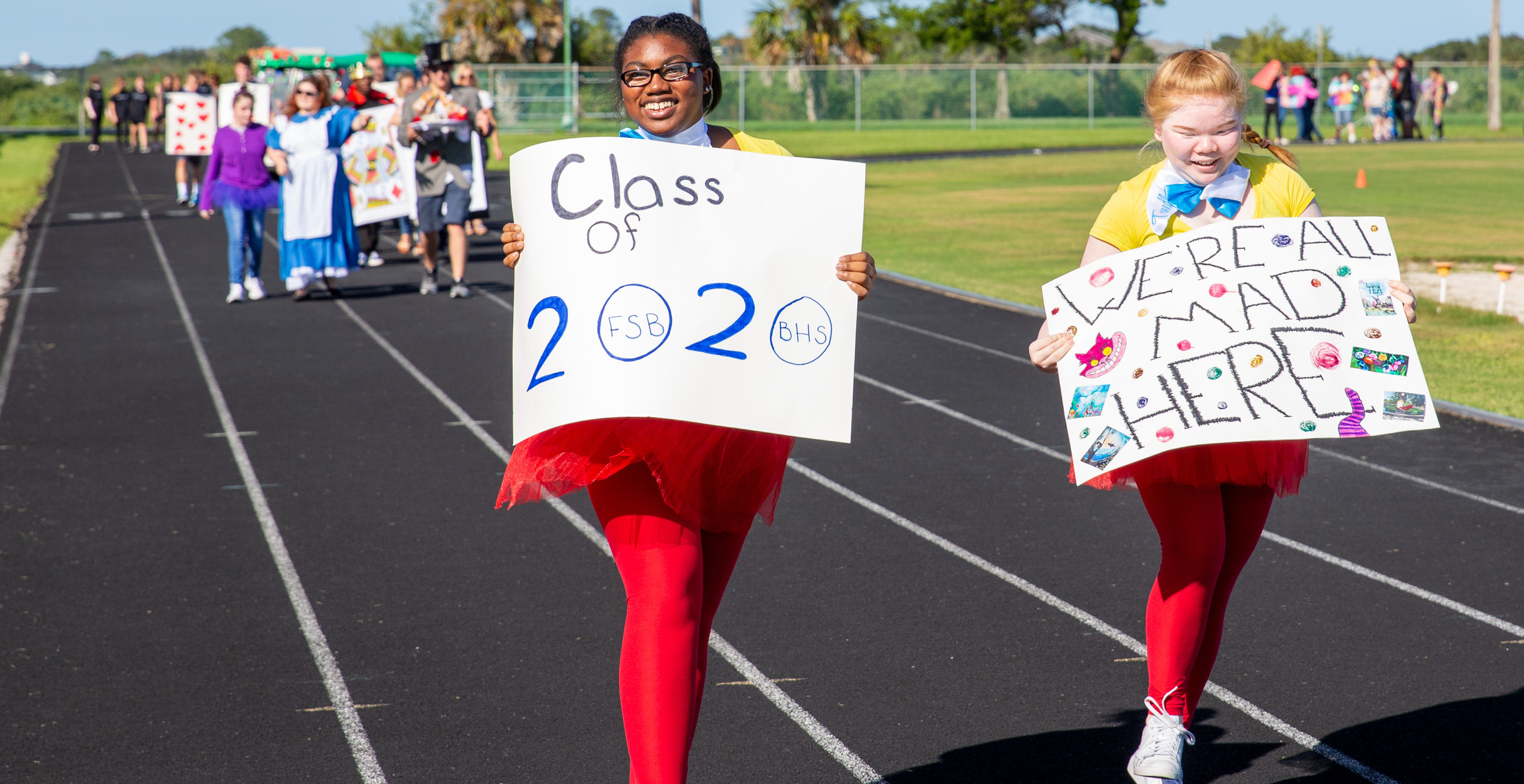 """Two senior girls dressed as Tweedle Dee and Tweedle Dum from Alice In Wonderland holding signs that read """"Class of 2020"""" and """"We're All Mad Here."""""""