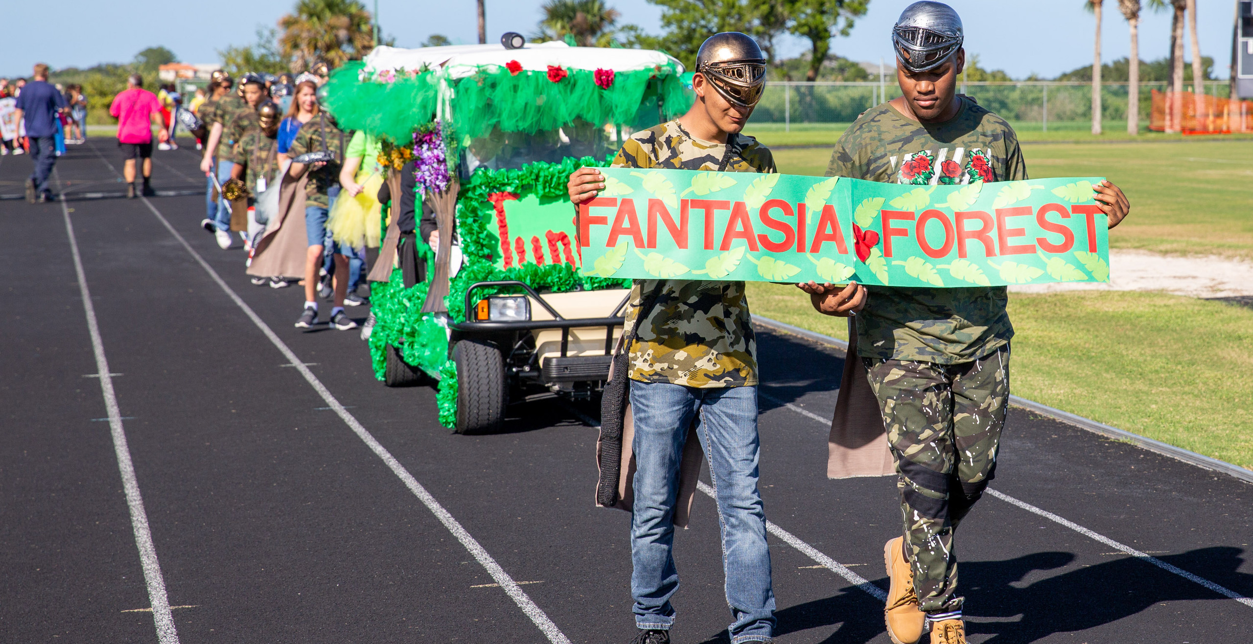 """Junior class marching down track with a decorated golf cart and a sign that reads, """"Fantasia Forest"""""""