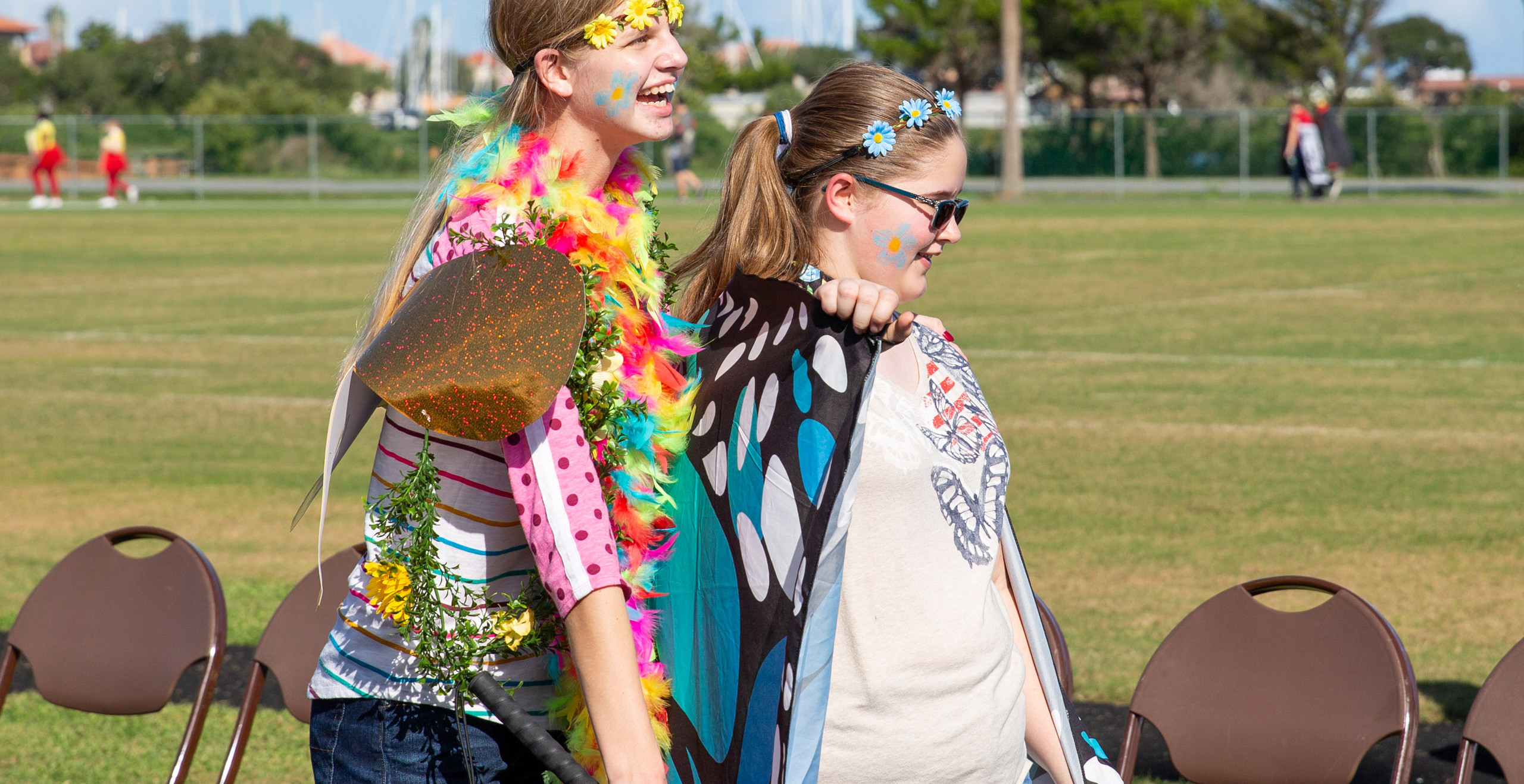 Two freshmen girls dressed as butterflies walking in the parade.