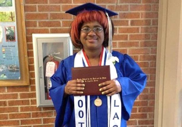 Jasmyn Polite holding her high school diploma.