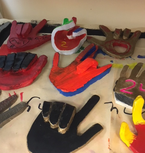 Different handshapes made out of clay and painted in mulitple colors.
