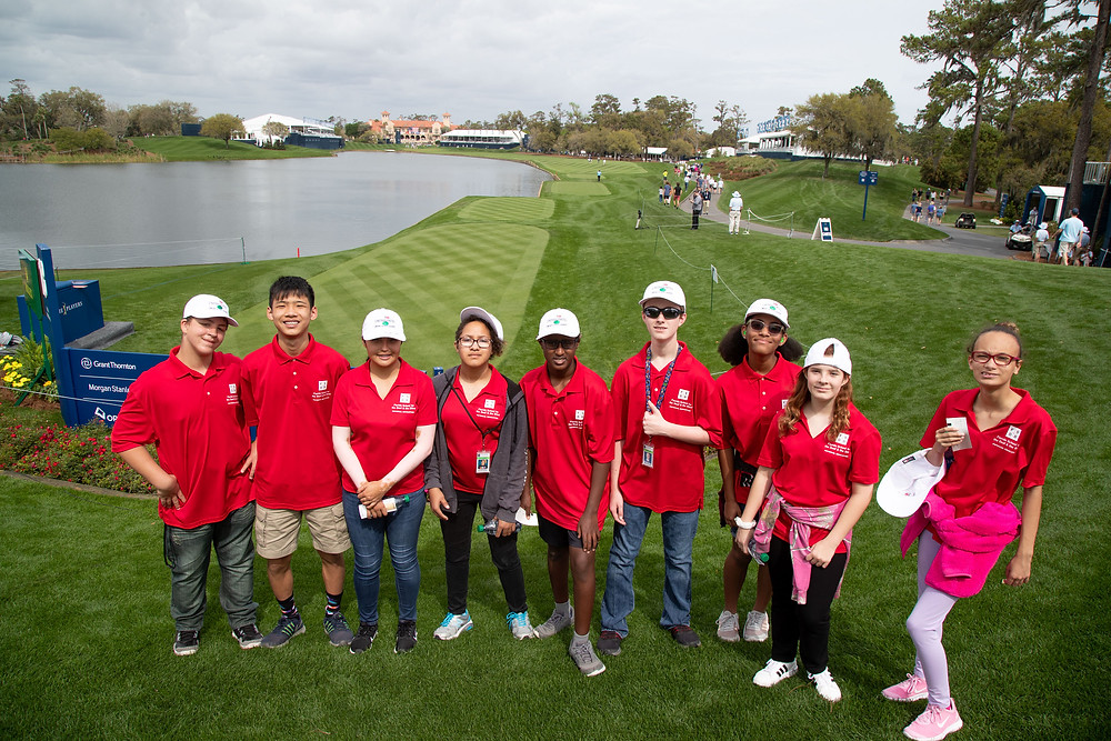 Students pose for photo with the 18th hole of TPC behind them.
