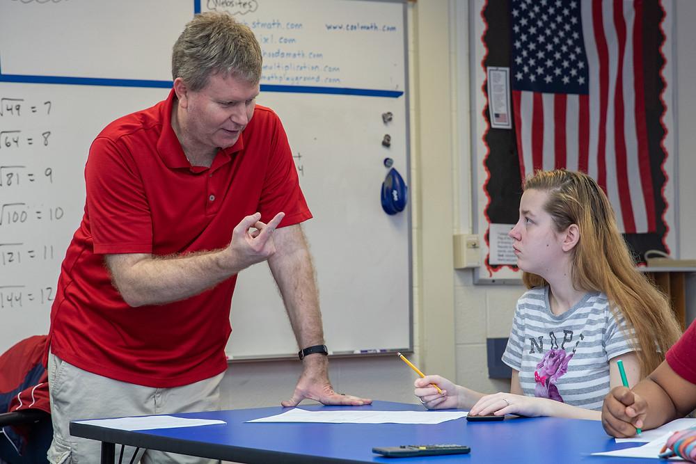 Matt Smith helping a deaf girl with a math worksheet.