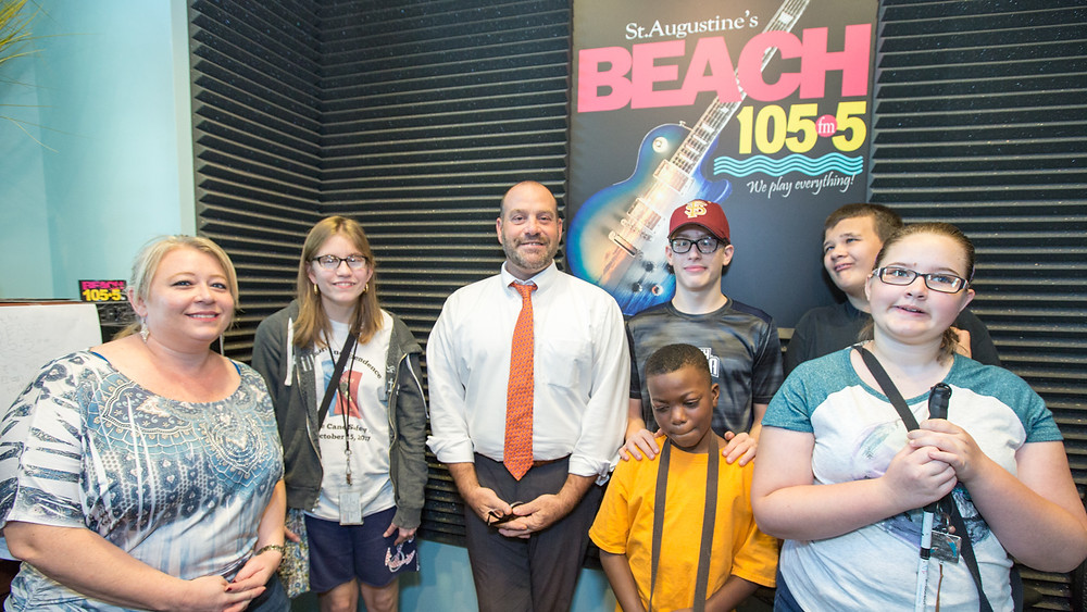 Blind students take a photo with the radio hosts from Beach 105.5 FM