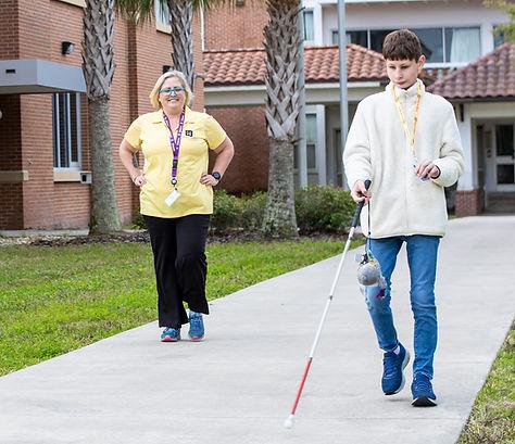 Blind boy using cane as an O&M teacher looks on.