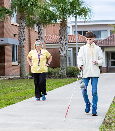 Blind student using cane with O&M teacher watching from behind.