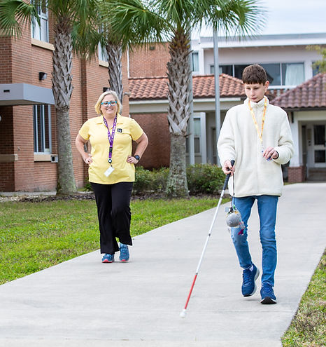 Blind boy walking with cane while O&M Teacher watches from behind.