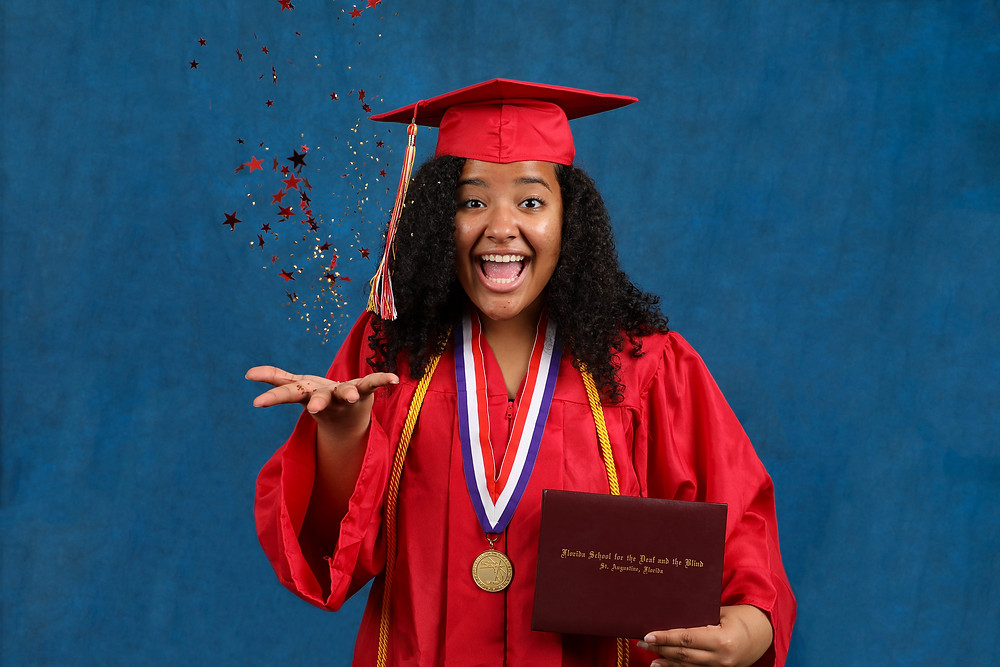 Brieara Warren wearing red cap and gown, throws glitter stars in the air with one hand and holds a diploma in the other.