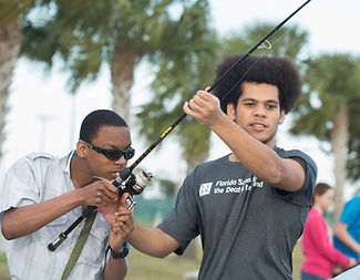 A deaf student helps a blind student learn how to fish in the recreation program.