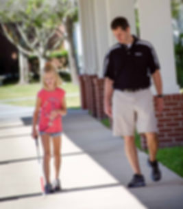 FSDB blind student walking with cane as Orientation and Mobility instructor walks alongside.