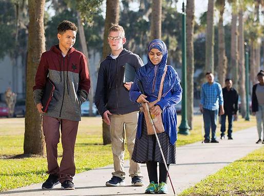 Three FSDB blind students walk down Palm Row