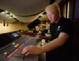 FSDB blind student operates sound board in auditorium