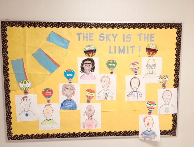 "Bulletin board with hand drawn people with the words ""The Sky is the Limit!"" at the top."