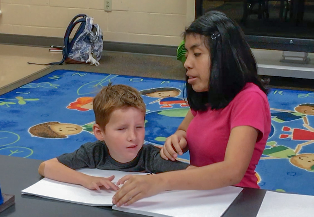 Meliza helping an FSDB blind elementary boy read braille.