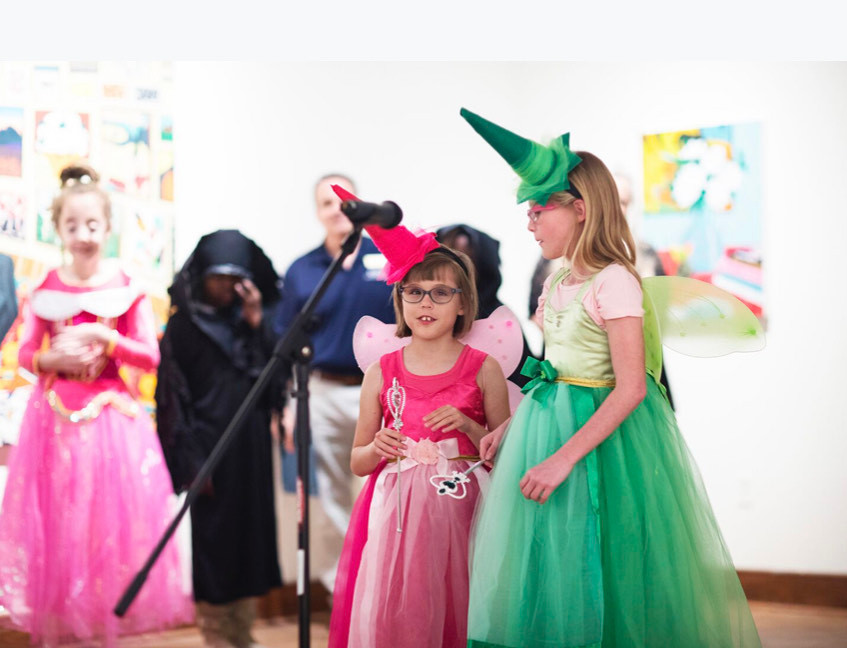 Two blind girls dressed as fairies sing into a microphone.