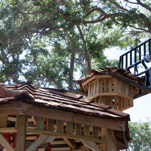 An FSDB student helps guide the cupola into place on top of the gazebo