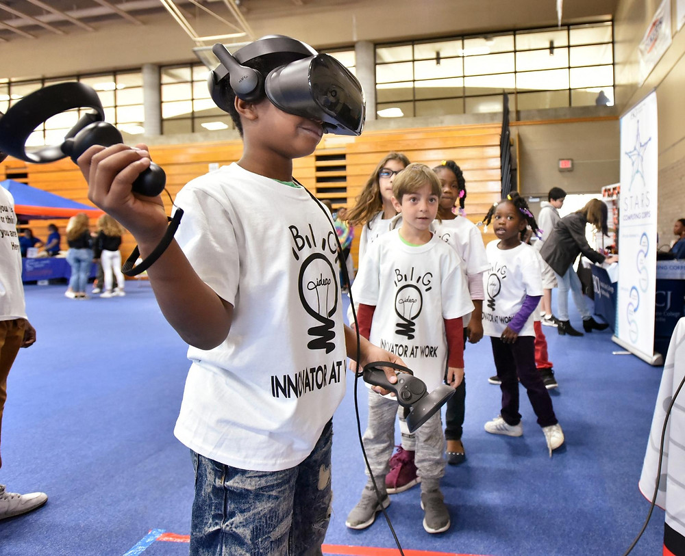 Student playing a mixed-reality computer game at science festival