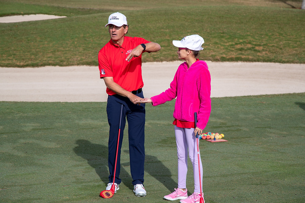 Rob Strano demonstrating how to hold a golf club with a student.