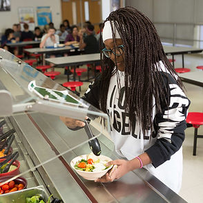 An African-American girl making a salad in the lunch line.