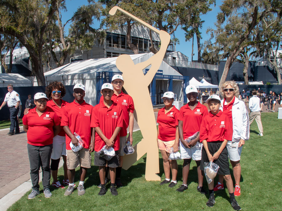 FSDB students pose for photo with TPC Logo of a golfer swinging.