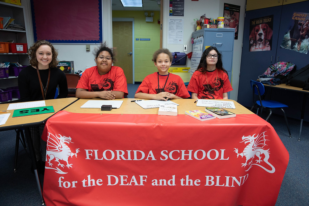 "Three students and a teacher from the ""Buff"" team sit a table and smile at camera."