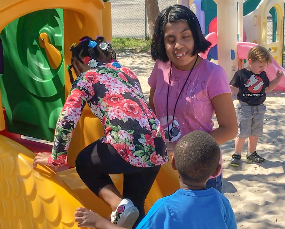 FSDB post grad student Meliza Lorenzo helping children down a slide.