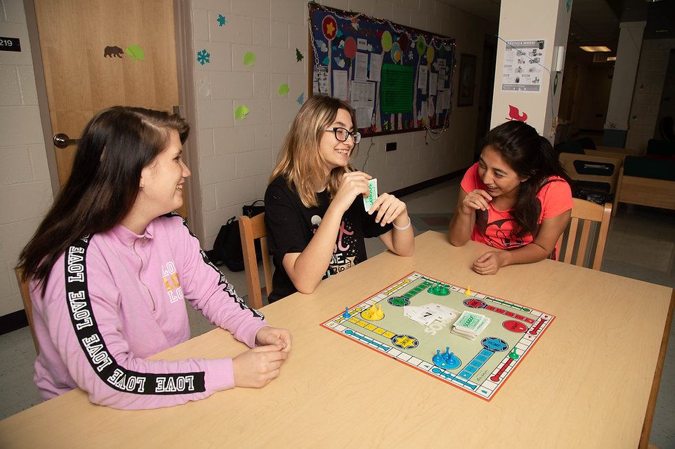 Deaf middle school girls playing a board game in the dorm.