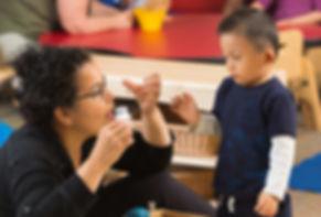 "FSDB teacher in toddler program signing ""Milk"" to deaf boy."