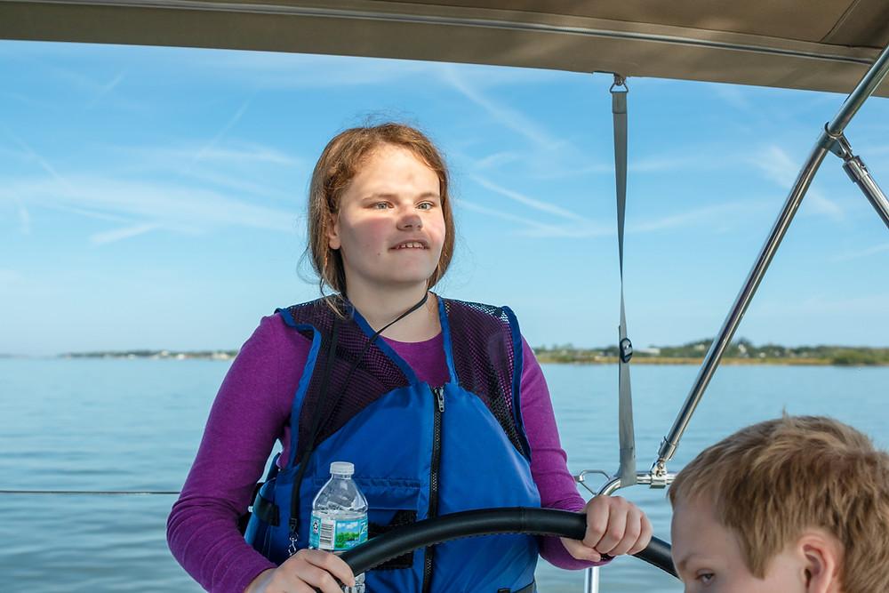 Blind girl steering sailboat.