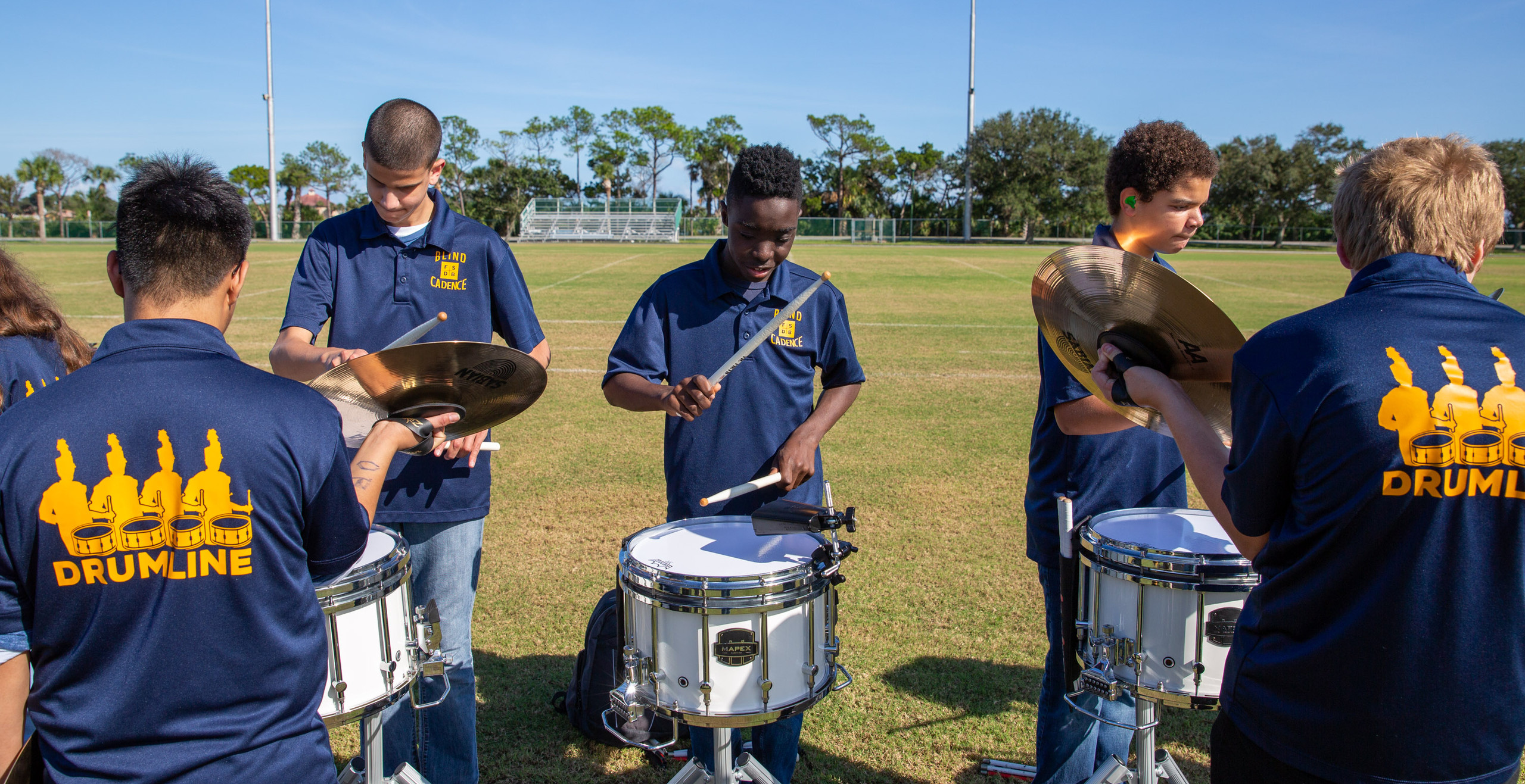 Drumline performing at homecoming. Three students hitting snare drum while two students hold cymbals in front of them.