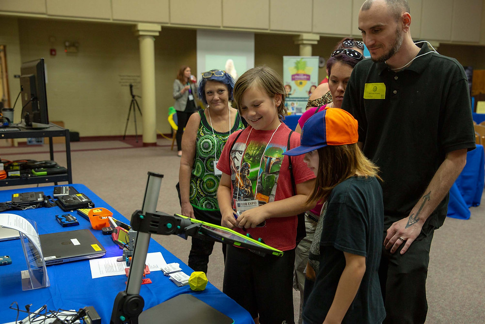 Visitors looking at assistive technology during the FSDB Expo.