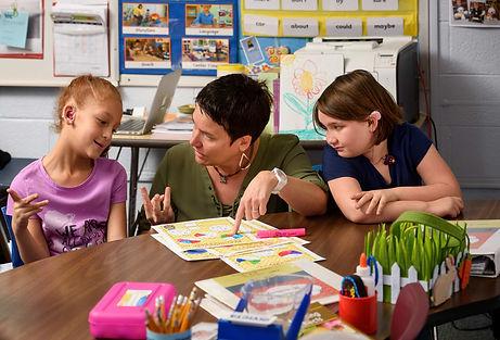 FSDB deaf elementary teacher helps two girls with a math problem.