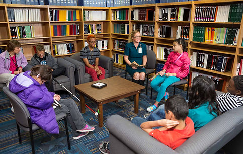 Librarian reading a book to blind students in library.