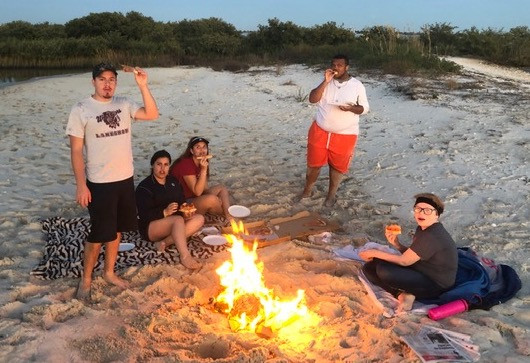 FSDB students in the Deaf Outdoors Club sitting around campfire on the beach eating smores.
